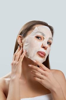 뷰티 페이셜 마스크. 얼굴에 천 보습 마스크와 아름 다운 젊은 여자. 피부 관리