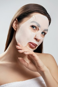 뷰티 페이셜 마스크. 얼굴에 천 보습 마스크를 가진 여자입니다. 피부 관리. 화장품 스파 마스크입니다. 페이셜 트리트먼트