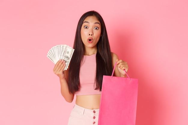 美容、ファッション、ライフスタイルのコンセプト。トレンディな服を着て、買い物袋とお金を持って、ピンクの壁の上に立って、店で現金を使っている美しい驚いたアジアの女性は、驚いているように見えます。
