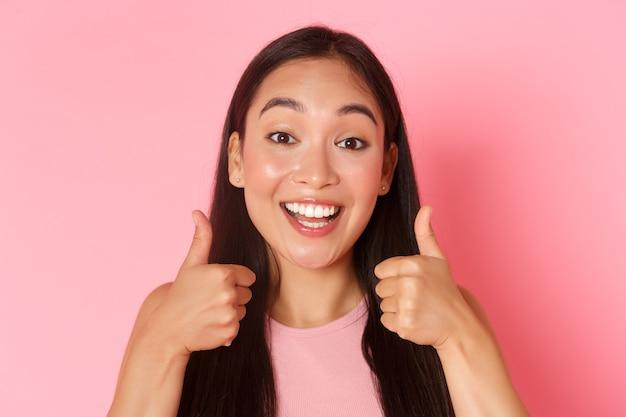 Концепция красоты, моды и образа жизни. крупный план очаровательной азиатской девушки, которая выглядит довольной, улыбается, довольна белыми зубами, показывает большие пальцы, делает комплимент хорошим выбором, хвалит или что-то любит.