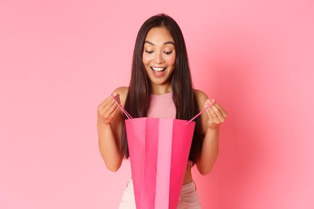 美容、ファッション、ライフスタイルのコンセプトです。ピンクの壁に立って幸せな明るい笑顔で買い物袋を探して、現在開いている興奮して驚いた、驚いた女の子のクローズアップ