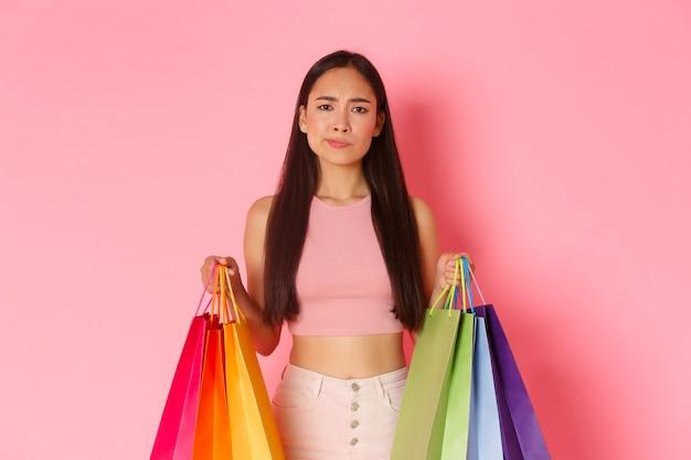 Концепция красоты, моды и образа жизни. крупный план нерешительной, скептически настроенной азиатской девушки с невеселой и обеспокоенной ухмылкой, держащей сумки с покупками и неуверенной в чем-то, розовая стена