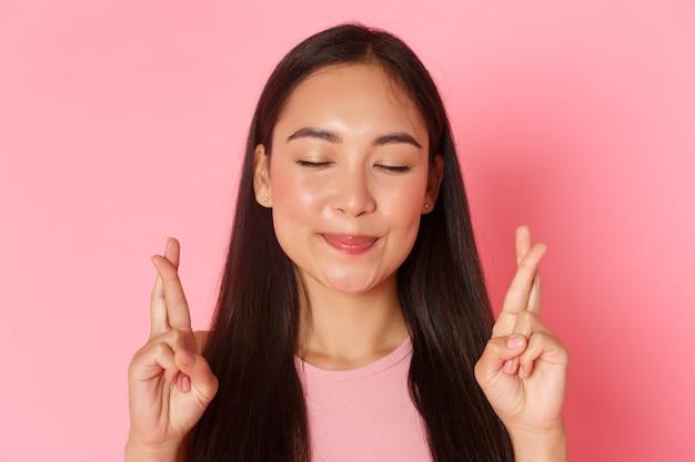 目を閉じて願い事をする希望に満ちた楽観的なアジアの女の子の美容ファッションとライフスタイルのコンセプトのクローズアップ...