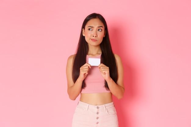 美容、ファッション、ライフスタイルのコンセプトです。決断を下し、クレジットカードを所持し、考え、何を買うかを選択し、ピンクの壁に立っている、優柔不断で真剣に見えるかなりアジアの女の子