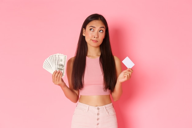 美容、ファッション、ライフスタイルのコンセプトです。優柔不断で思いやりのある魅力的なアジアの女の子が選択し、お金とクレジットカードの両方を持ち、左上隅を見て、非接触型または現金で買い物をしています。