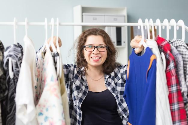 美容、ファッション、人々のコンセプト-黒メガネで笑顔美人がドレスを選ぶ
