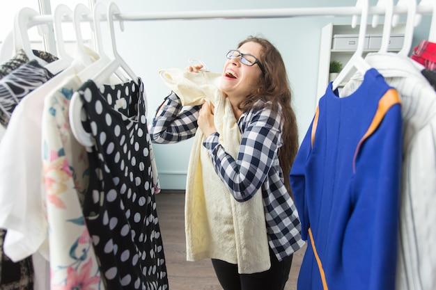 美容、ファッション、人々のコンセプト-黒メガネで幸せな興奮した女性がドレスを選ぶ