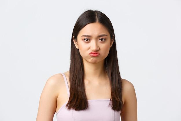 Красота, мода и концепция эмоций людей. портрет крупным планом надутой расстроенной милой азиатской девушки с гримасой