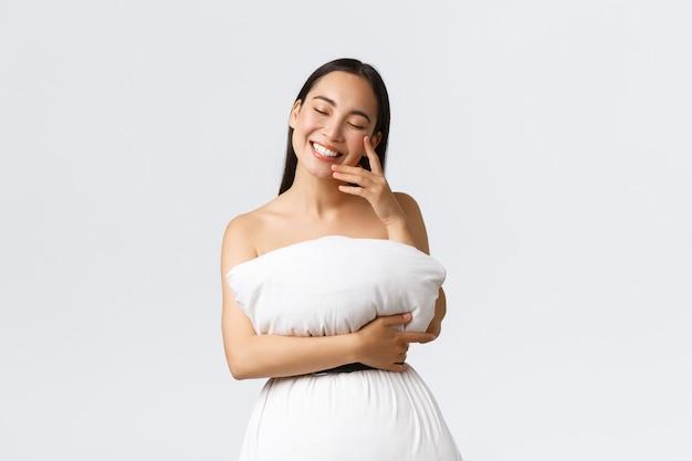 Красота, мода и концепция социальных сетей. великолепная женщина-блогерша женственного образа жизни, одетая в подушку, как платье, прикреплена к телу ремнем вокруг отходов, смеется и радостно улыбается