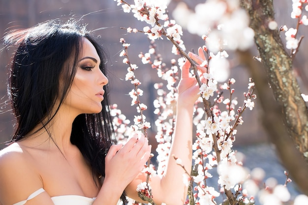 Beauty and fashion beautiful woman near spring blooming park