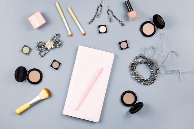 Красота, мода блоггер концепция. модные аксессуары, записная книжка и косметика на сером фоне плоской планировки.