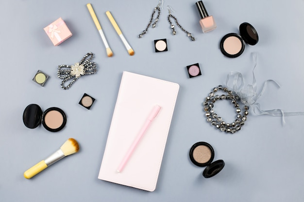 Beauty, fashion blogger concept. fashion accessories, note book and cosmetics on grey background flat lay.
