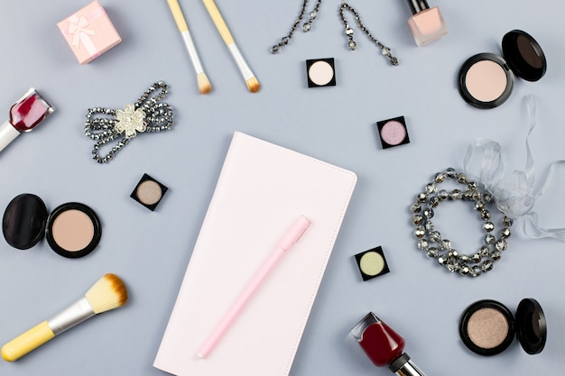 Beauty, fashion blogger concept. fashion accessories, note book and cosmetics on grey surface flat lay.