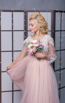彼女の手に花の花束を持つインテリアスタジオで美容ファッション花嫁。美しい花嫁の肖像画の結婚式のメイクや髪型。