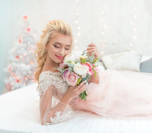 Невеста моды красоты в зимнем декоре с букетом цветов в ее руках.