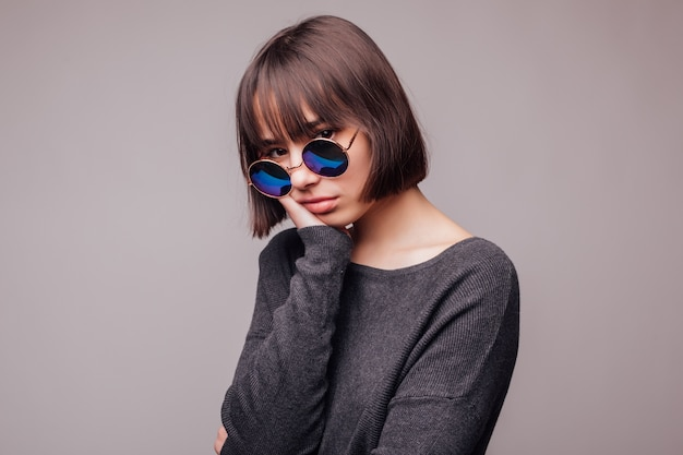 Ragazza castana di modo di bellezza che porta gli occhiali da sole alla moda. ritratto di donna sexy con isolato sul muro grigio.