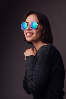 Ragazza di modello giovane brunetta di modo di bellezza che indossa occhiali da sole alla moda isolati su grey. fashion blogger