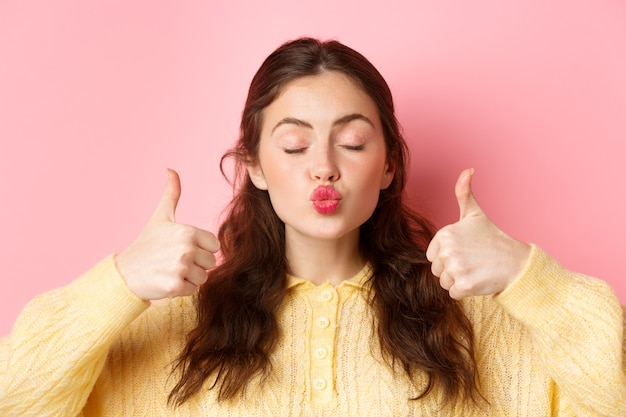 Beauty and fashion. close up portrait of lovely and coy girl pucker lips with eyes closed, showing thumbs up in approval, praise something good, standing against pink wall.