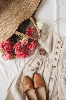 Beauty fashion composition with female sun dress sarafan, shoes, pink peony flowers in straw bag on linen. flat lay, top view
