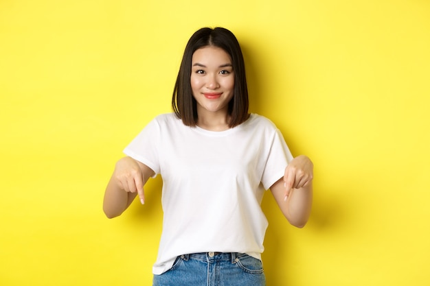 Beauty and fashion concept. beautiful asian woman in white t-shirt pointing fingers down, demonstrate logo standing over yellow background