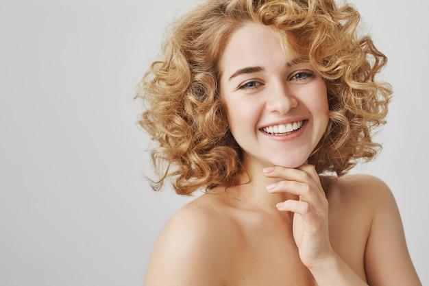 Concetto di moda e bellezza. bella ragazza spensierata con capelli ricci e spalle nude sorridenti