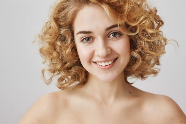 Concetto di moda e bellezza. affascinante ragazza dai capelli ricci con spalle nude sorridente