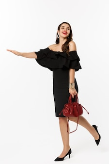 Beauty and fashion concept. full length of glamour woman in black dress and high heels raising hand to stop taxi, need a ride, standing over white background.