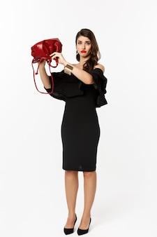 Concetto di bellezza e moda. tutta la lunghezza della giovane donna triste in abito nero e tacchi alti che mostra la borsa vuota, imbronciata delusa, in piedi su sfondo bianco.