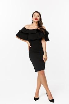 Concetto di moda e bellezza. colpo integrale di bella donna castana che indossa un abito nero di lusso e tacchi sulla festa, sorridente con le labbra rosse, in piedi su sfondo bianco.