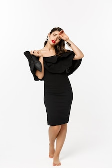 Concetto di bellezza e moda. integrale della giovane donna stanca in vestito nero elegante, togliendosi i tacchi alti e guardando esausto, in piedi su sfondo bianco.