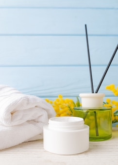 Beauty and fashion concept with spa set. cream, towel and yellow flowers and incense sticks.
