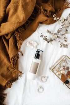 Красота, мода образ жизни женский коллаж. бутылка крема, ветка эвкалипта, имбирный плед, бижутерия на белом белье.