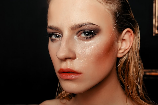 Beauty fashion model girl natural makeup wet hair on black gold background in warm tones. portrait of young woman with fashion makeup