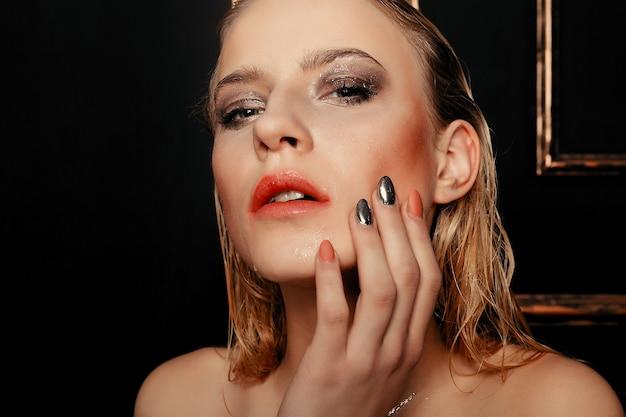 Красота фотомодель девушка естественный макияж мокрые волосы на фоне черного золота в теплых тонах. портрет молодой женщины с модным макияжем