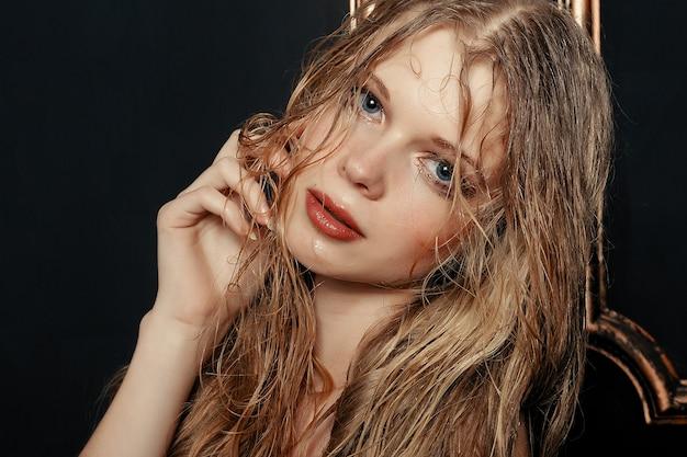温かみのある色調のブラックゴールドの背景に美容ファッションモデルの女の子のナチュラルメイク濡れた髪。ファッションメイクと若い女性の肖像画