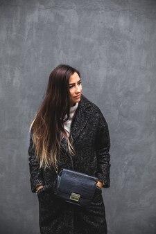 スタイリッシュなコートを着た美容ファッションモデルの女の子。美容トレンド。灰色で隔離。ファッションブロガー