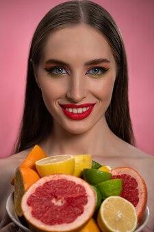 Девушка фотомодели красоты с красивым макияжем, красными губами, длинными здоровыми волосами и ярким криком