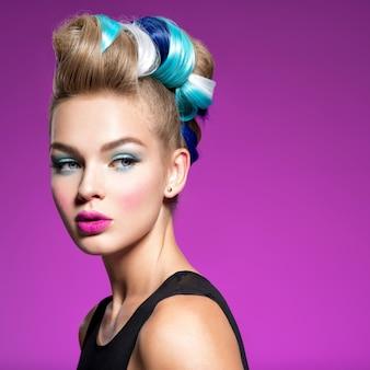Девушка фотомодели красоты с красочными крашеными волосами. девушка с голубым макияжем и прической. синий макияж. студия.