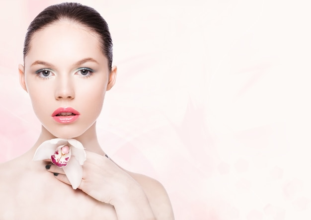 ピンクのボケ味の背景にスパで白い蘭を保持している美容ファッションモデル