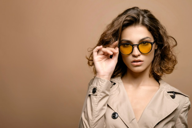 Beauty fashion model with clean skin and curly hair in beige cloak stretch on beige wall, model in fashion glasses