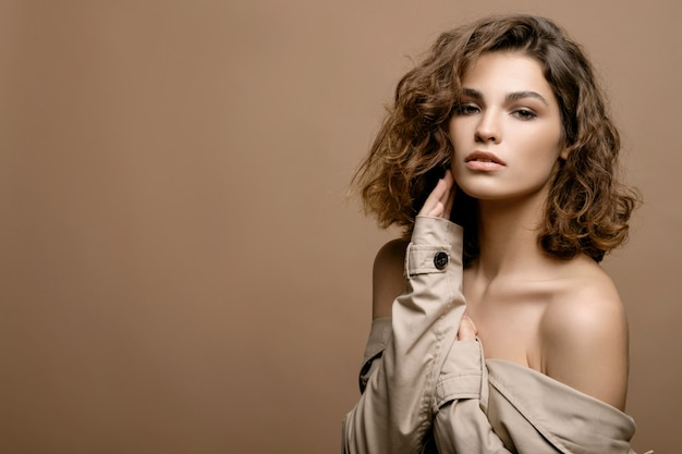 Beauty fashion model with clean skin and curly hair in beige cloak stretch with scarf on beige wall, copy space