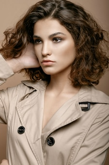 Beauty fashion model with clean skin and curly hair in biege cloak stretch with scarf