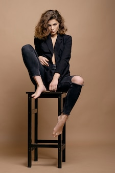 Beauty fashion model with clean skin and curly hair in black jacket on the chair, serious business woman