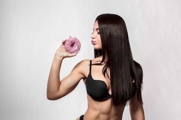 Beauty fashion model woman taking colorful donuts