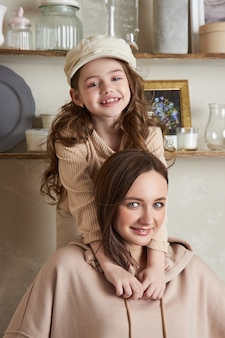 Beauty fashion mom and daughter. family photo shoot, joy and fun emotions. woman and a girl embrace