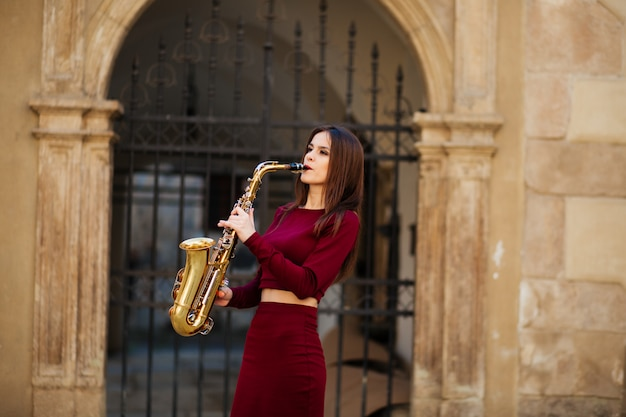 Beauty and fashion, music. pretty woman with saxophone.