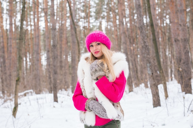 Beauty, fashion, people concept - attractive blond woman walking in pink hat and sweaters in winter