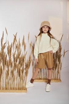 白い背景の上の春の草の美容ファッションの肖像画の女の子。女の子の顔に笑顔