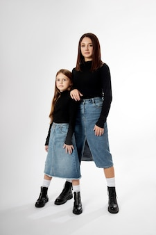 Beauty fashion portrait mother and daughter in a black turtleneck and blue denim skirt. woman and girl, family