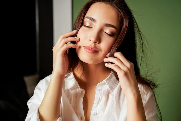 Портрет моды красоты чувственного закрывая глаза азиатская молодая женщина с темными длинными волосами в белой рубашке